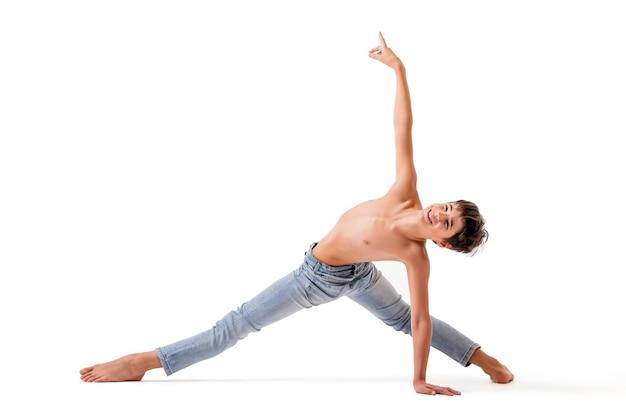 Un danseur de ballet adolescent pose dans un étirement pieds nus, isolé sur un fond blanc.
