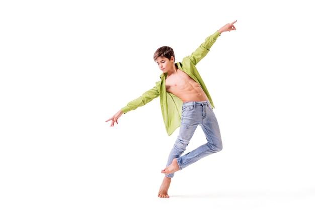 Un danseur de ballet adolescent pose pieds nus, isolé sur fond blanc.