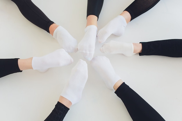 Danseur de ballet attachant des chaussures de ballet. bouchent la fille de ballet mettant ses chaussures de pointe assis sur le sol, arrière-plan flou.