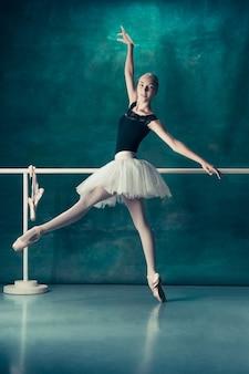 Le danseur de ballet classique en tutu blanc posant à la barre de ballet sur fond de studio