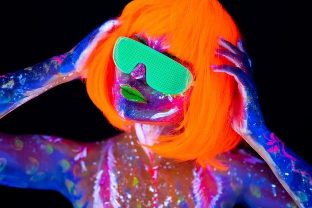 Danseur disco en néon. mannequin femme en néon, portrait de belle fille modèle avec maquillage fluorescent, body art design en uv, visage peint, maquillage coloré, sur fond noir