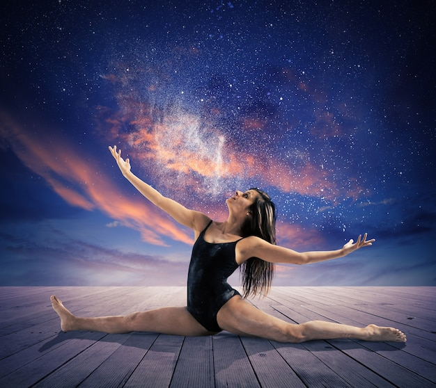 Le danseur fait une scission sous les étoiles dans le ciel