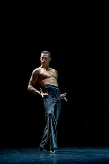 Danseur de salon musculaire seins nus faisant pose isolé sur fond noir.