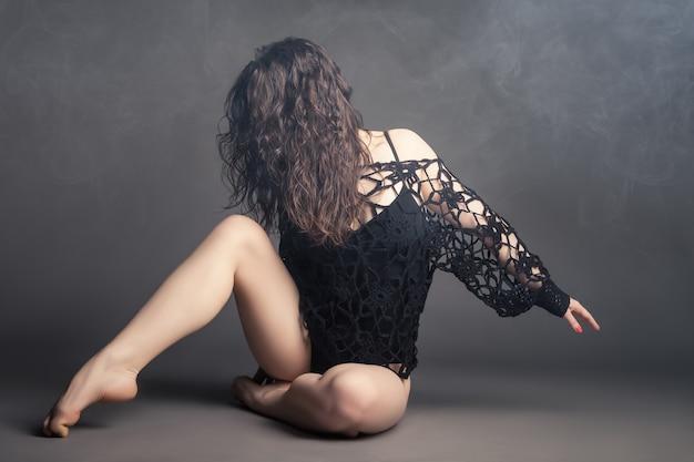 Danseur de style moderne posant sur un fond gris studio dans le brouillard