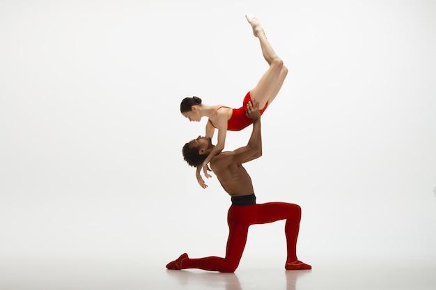 Danseurs de ballet classique gracieux dansant isolé sur fond de studio blanc. couple dans des vêtements rouge vif comme une combinaison de vin et de lait. le concept de grâce, d'artiste, de mouvement, d'action et de mouvement.