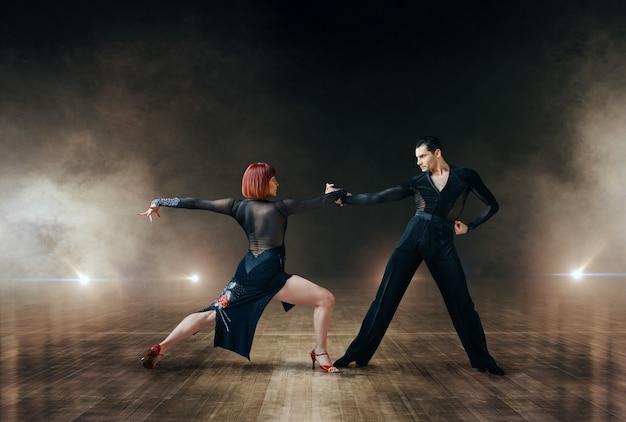 Danseurs élégants en costumes, danse latine sur scène. partenaires féminins et masculins sur un couple professionnel dansant sur une scène de théâtre