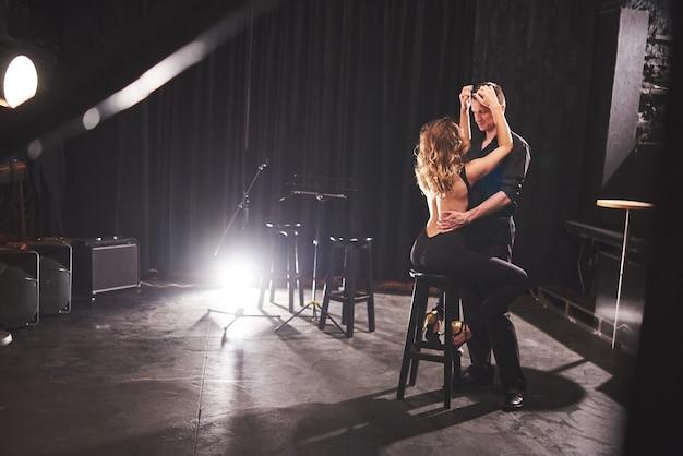 Danseurs habiles exécutant dans une pièce sombre sous la lumière.