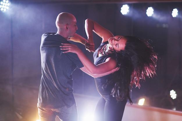 Danseurs habiles se produisant dans la pièce sombre sous la lumière du concert et la fumée. couple sensuel exécutant une danse contemporaine artistique et émotionnelle