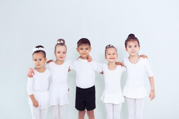 Danseurs mignons de petits enfants sur fond blanc danse chorégraphiée par un groupe de petites ballerines