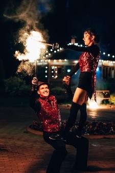 Des danseurs professionnels, hommes et femmes, présentent un spectacle de feu et une performance pyrotechnique