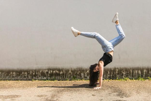 Danseuse active faisant le poirier à l'extérieur