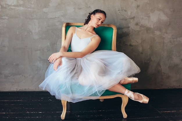 Danseuse ballerine en belle robe bleu clair jupe tutu posant assis sur une chaise de vinage en studio loft