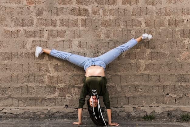 Danseuse habile faisant main debout étirer sa jambe