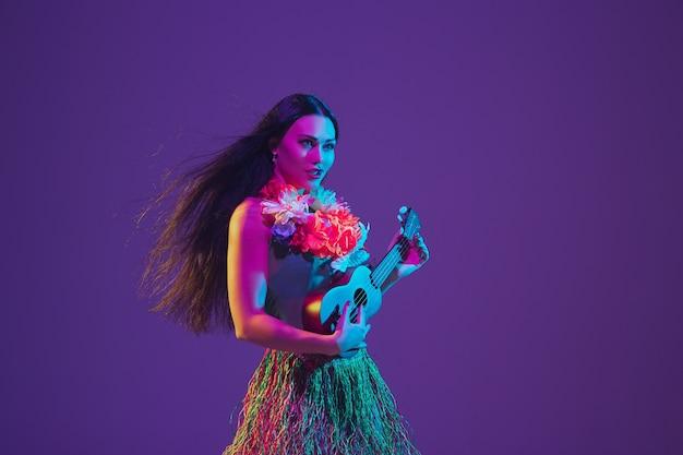 Danseuse hawaïenne sur mur violet à la lumière du néon.