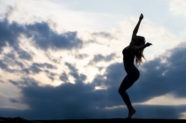 Danseuse de jeune femme sur le lever du soleil en plein air.
