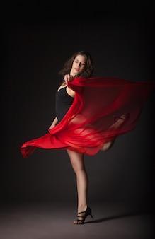 Danseuse moderne avec tissu rouge posant sur gris