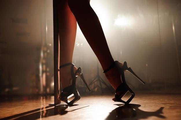Danseuse à la perche, jambes sexy près d'un pylône.