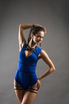 Danseuse de pole femme sexy portant un body bleu et des talons hauts sur fond gris