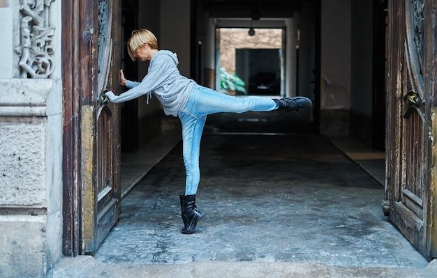 Danseuse professionnelle soulevant sa jambe et l'autre pied sur la pointe des pieds, s'appuyant sur une porte en bois d'un immeuble. danse urbaine