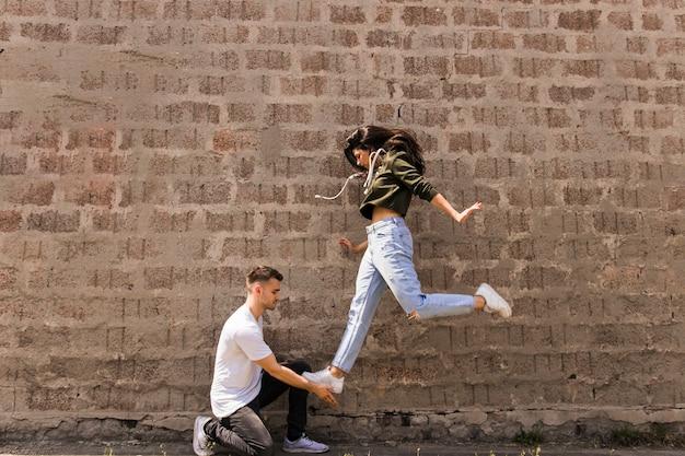 Danseuse sautant sur la main de l'homme contre le mur de pierre