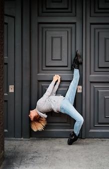 Une danseuse se tient à la porte d'un immeuble en levant la jambe et l'autre pied sur la pointe des pieds. danse urbaine