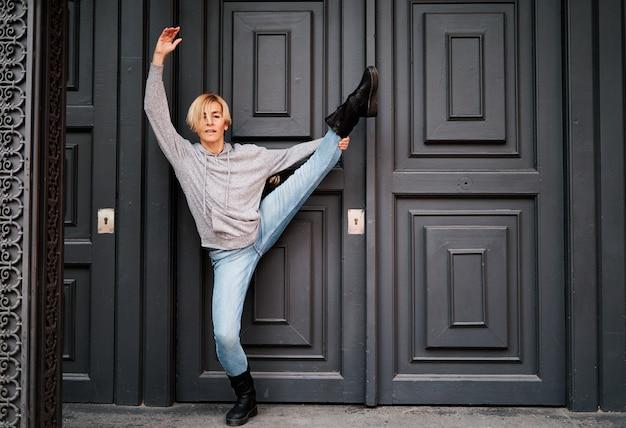 Danseuse se tient à la porte d'un immeuble avec un pied sur la pointe des pieds et l'autre vers le haut. danse urbaine