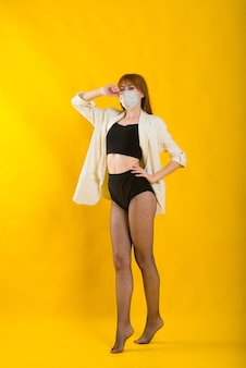 Danseuse de strip-tease en studio jaune en masque de protection de covid, body noir