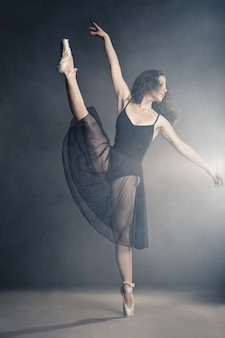 Danseuse de style moderne posant sur fond gris