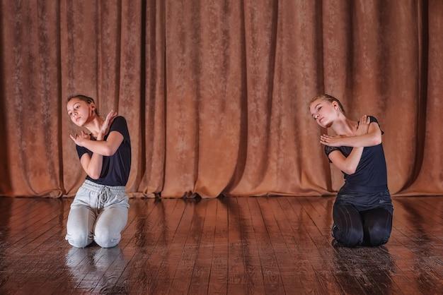 Les danseuses de jeunes filles travaillent sur des mouvements de danse sur scène.