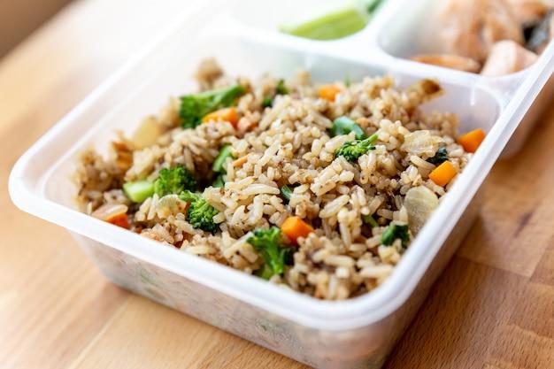 Darne de saumon bio coupée en dés avec riz sauté aux oignons, au brocoli et aux carottes.