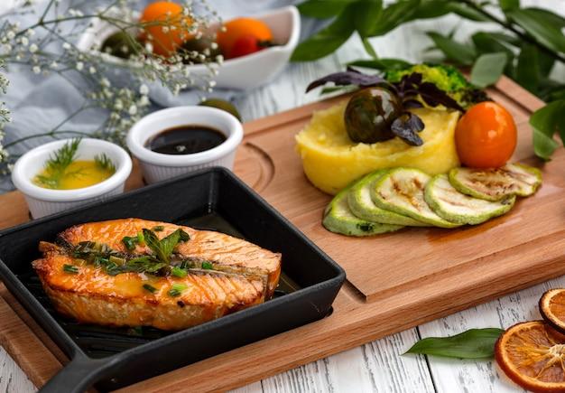 Darne de saumon rôti dans un plat en fonte servi avec purée de pommes de terre