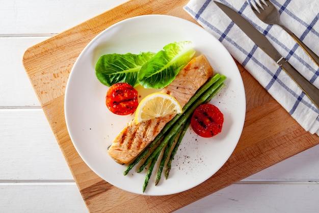 Darne de saumon rôti avec tomates asperges et légumes frais.