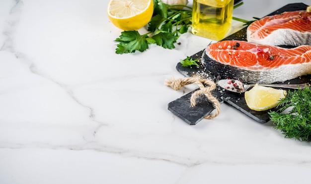 Darnes de poisson de saumon crues au citron, aux herbes, à l'huile d'olive, prêtes à être grillées, planche à découper en ardoise