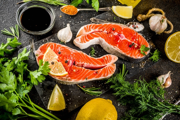 Darnes de poisson de saumon crues au citron, aux herbes, à l'huile d'olive, prêtes à être grillées