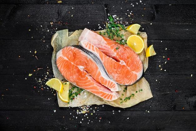 Darnes de saumon sur la vue de dessus de fond en bois noir