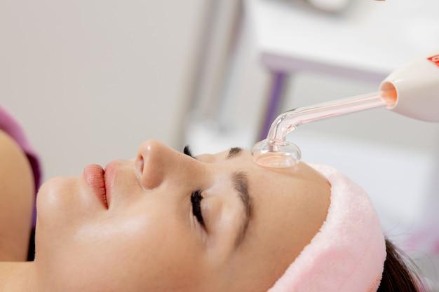 Darsonvalisation du visage ou rajeunissement du visage à l'aide de l'électrothérapie.