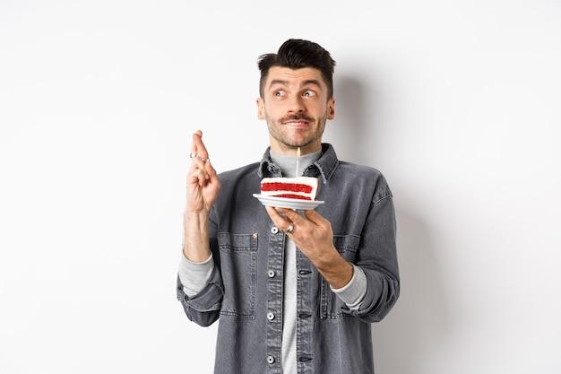 Date d'anniversaire. heureux jeune homme célébrant, faisant voeu avec gâteau et croiser les doigts, à la recherche d'espoir de côté, debout sur fond blanc.