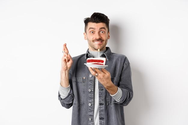 Date d'anniversaire. heureux mec faisant voeu avec les doigts croisés, tenant le gâteau bday avec bougie, debout sur fond blanc.