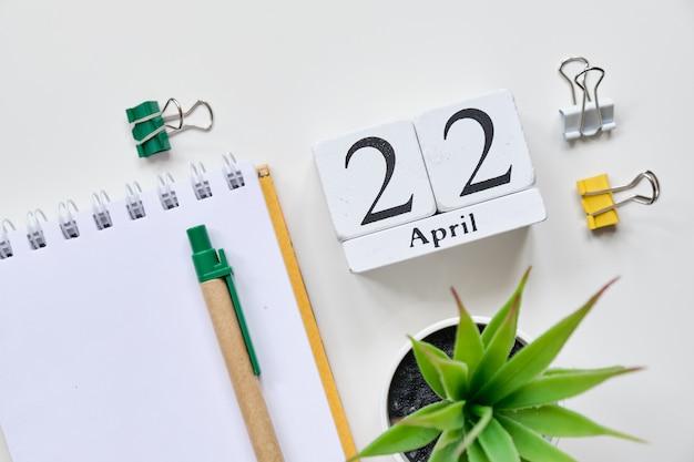 Date sur des cubes en bois blancs - le 22, 22 avril sur un tableau blanc. vue de dessus.