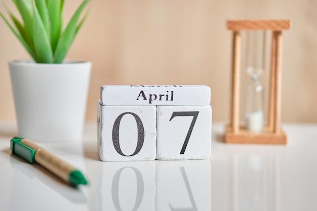 Date sur des cubes en bois blancs - le sept, 07 avril sur un tableau blanc.