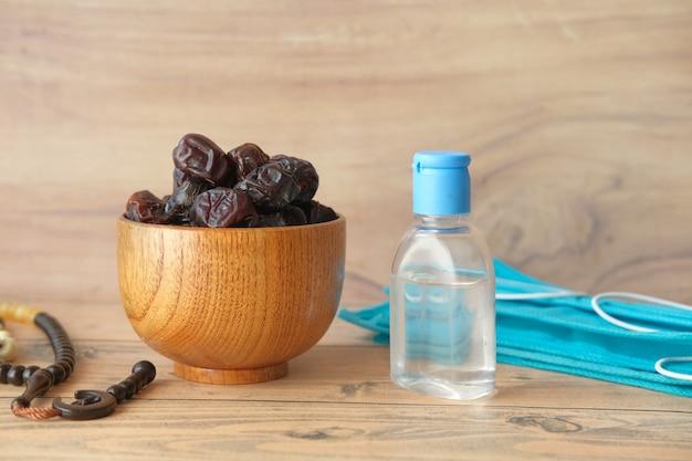Date de fruits frais dans un bol de désinfectant pour les mains chapelet de prière et masque sur table