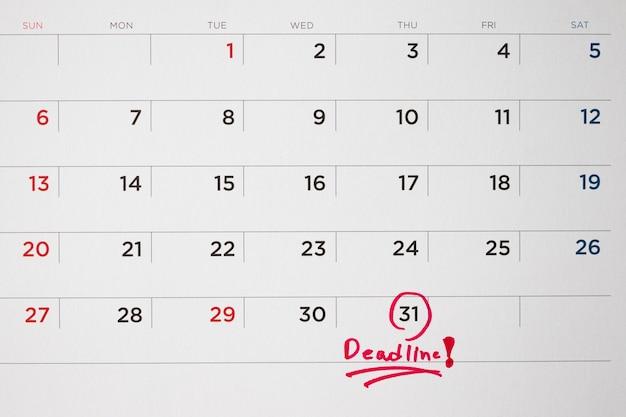 Date limite écrire sur la date de la page de calendrier blanc close up