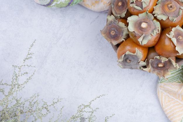 Date des prunes dans un plateau en bois sur fond gris