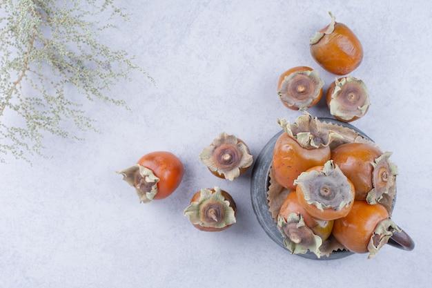 Date des prunes dans un pot métallique sur fond gris