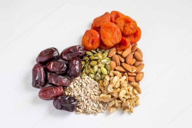 Dates, abricots secs, graines de citrouille, graines de tournesol, amandes, noix de grenoble sur fond blanc