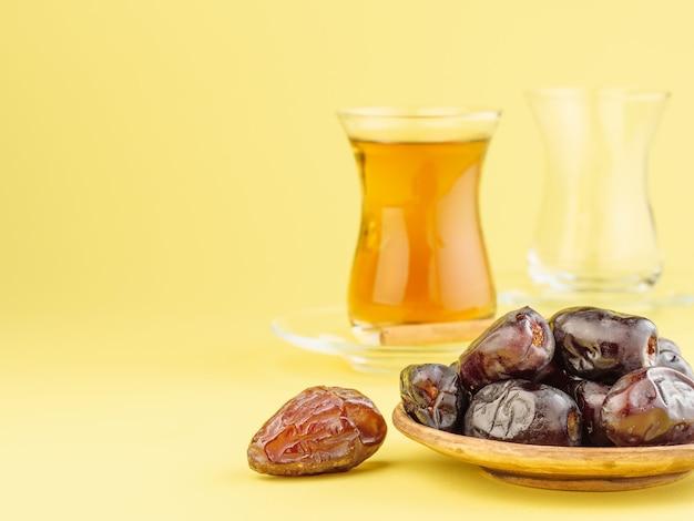 Dates au thé noir sur fond jaune. nourriture traditionnelle de l'iftar pendant le ramadan.