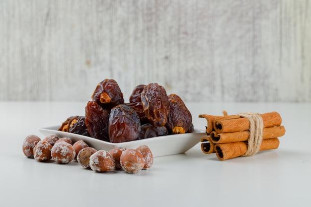 Dates avec des bâtons de cannelle et des noix dans une assiette, vue latérale.