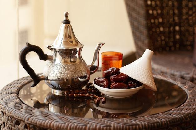 Dates dans une assiette en verre avec un couvercle, une boisson orientale et un chapelet sur une table en verre