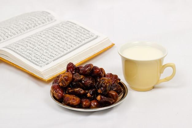 Dates du coran et un verre de lait isolé sur fond blanc