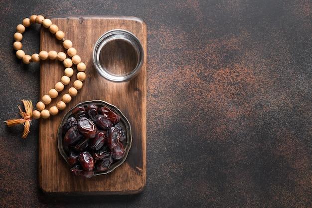 Dates du ramadan dans un bol verre d'eau perles de prière en bois sur la tradition religieuse marron eid mubarak